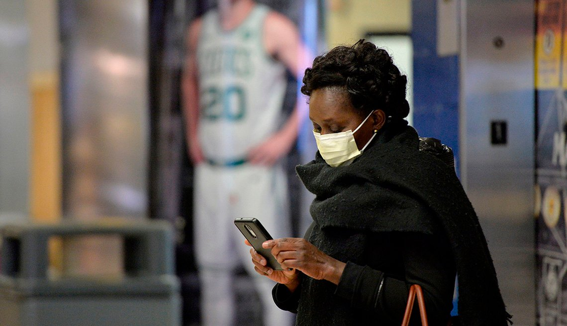 An African-American woman in a mask stands in TD Garden and checks her phone.
