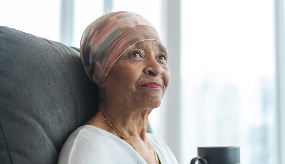 A black senior woman with cancer is wearing a scarf on her head and drinks tea.