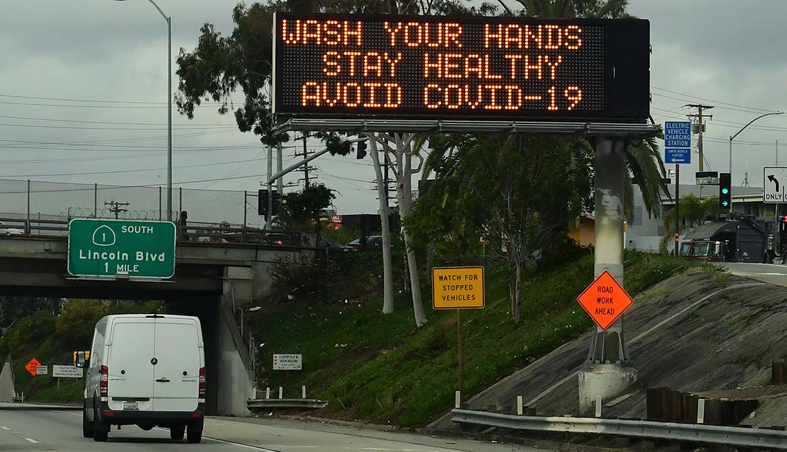 Vista de una autopista y un letrero electrónico que dice que laves tus manos y evites la COVID-19