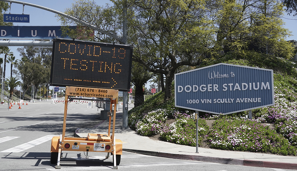 item 4 of Gallery image - a temporary l e d road sign that says covid nineteen testing with an arrow points to the entrance sign outside dodger stadium in los angeles