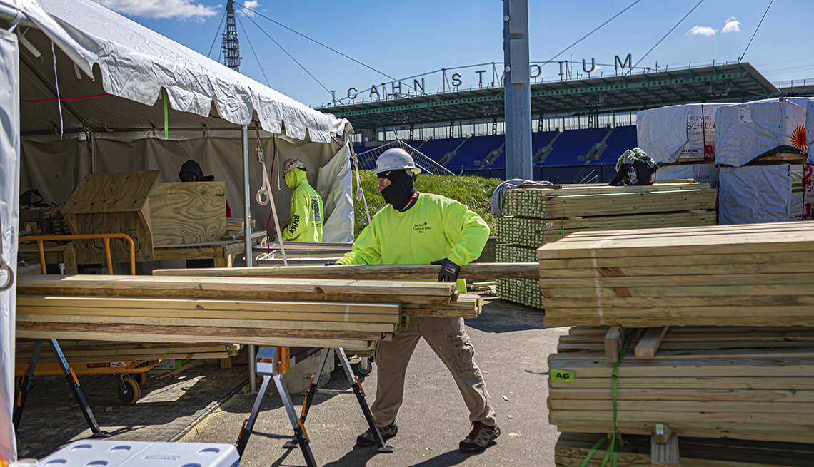 item 7 of Gallery image - workers build wooden shelves for morgue trailers outside icahn stadium in new york