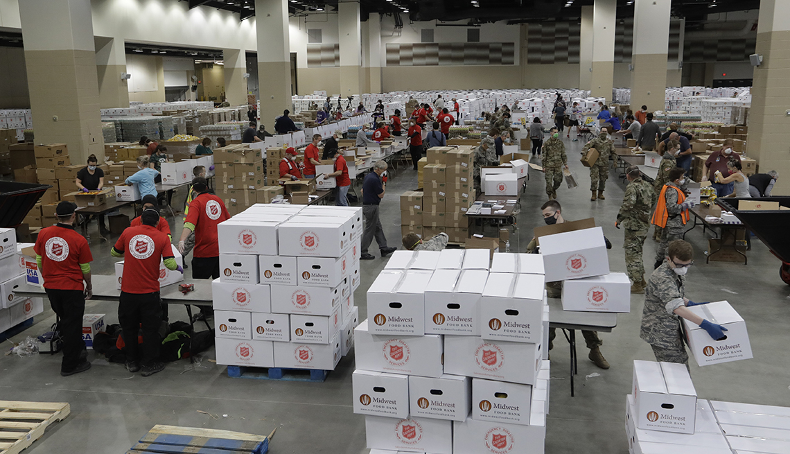 item 6 of Gallery image - indoor space of large sports stadium is filled with pallets of  food supplies and volunteers