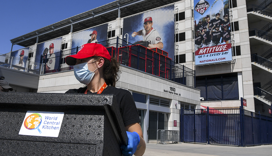 a masked and gloved worker helps load a crate of supplies from the world central kitchen outside nationals park in washington dc