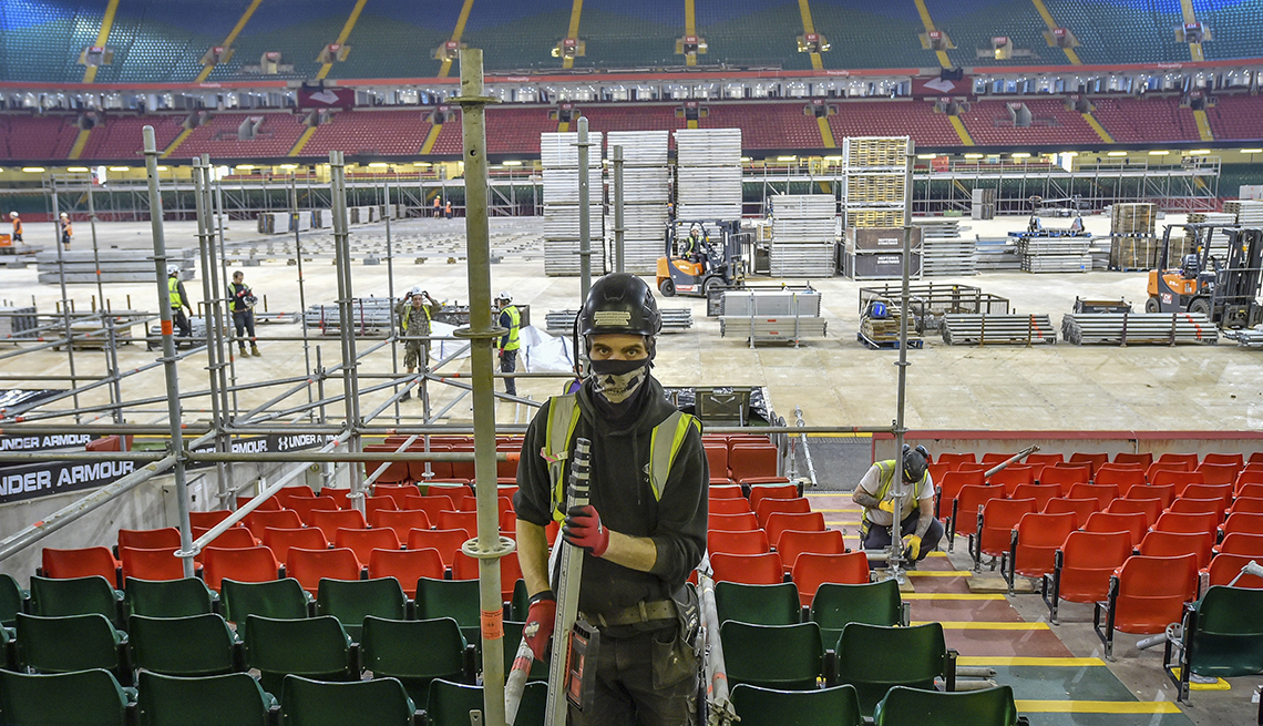 item 5 of Gallery image - a worker in gloves and a face mask is building scaffolding inside a stadium