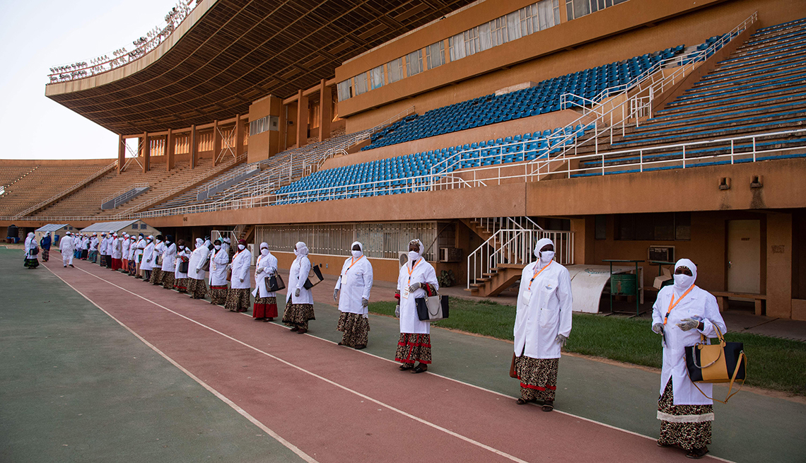 item 8 of Gallery image - masked medical staff in lab coats over long traditional dresses line up six feet apart at the edge of a stadium field