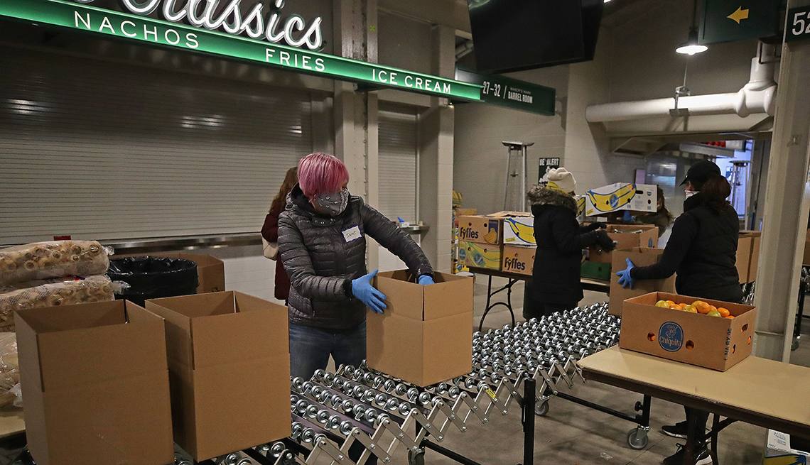 item 2 of Gallery image - four masked and gloved volunteers filling cartons with food in the concourse of a sports stadium