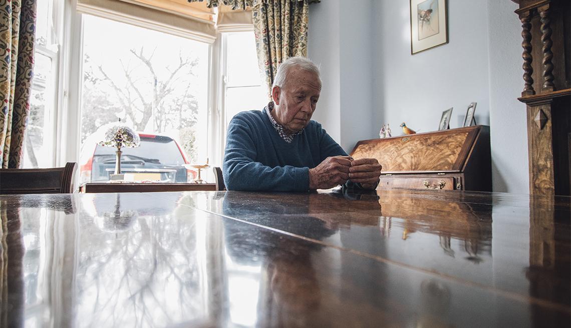 Un hombre mayor sentado en su mesa solo y triste