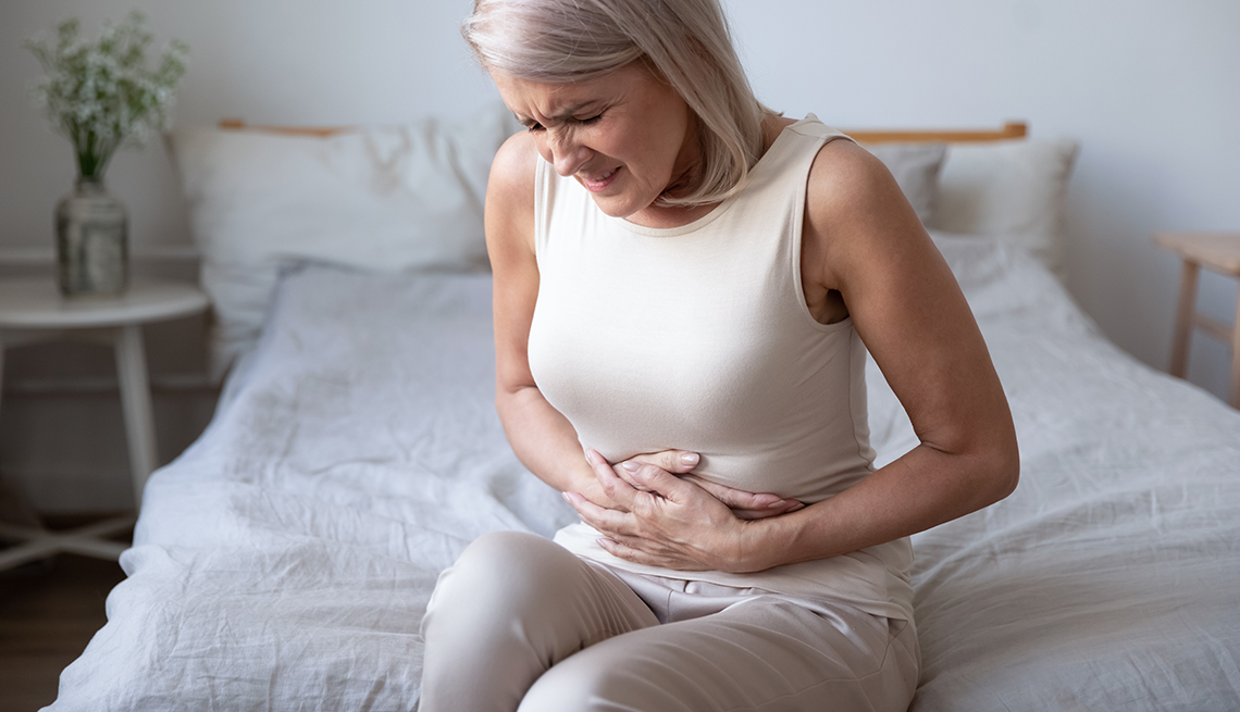 a woman sits on the edge of her bed holding her abdomen as if in pain