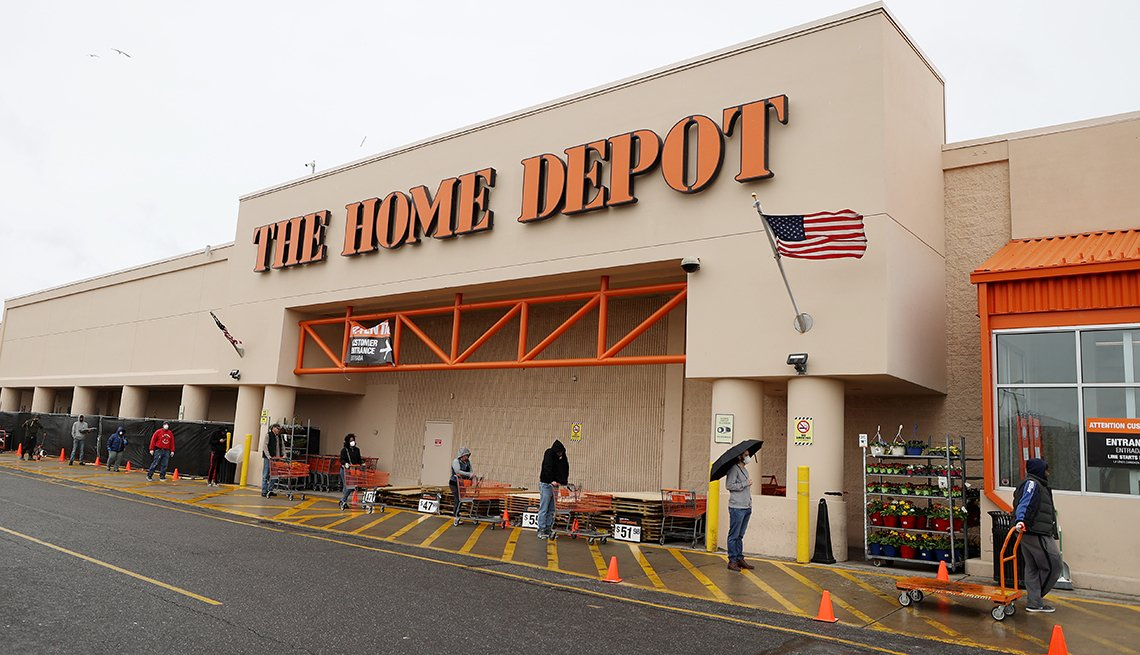People wearing masks and gloves wait to enter Home Depot