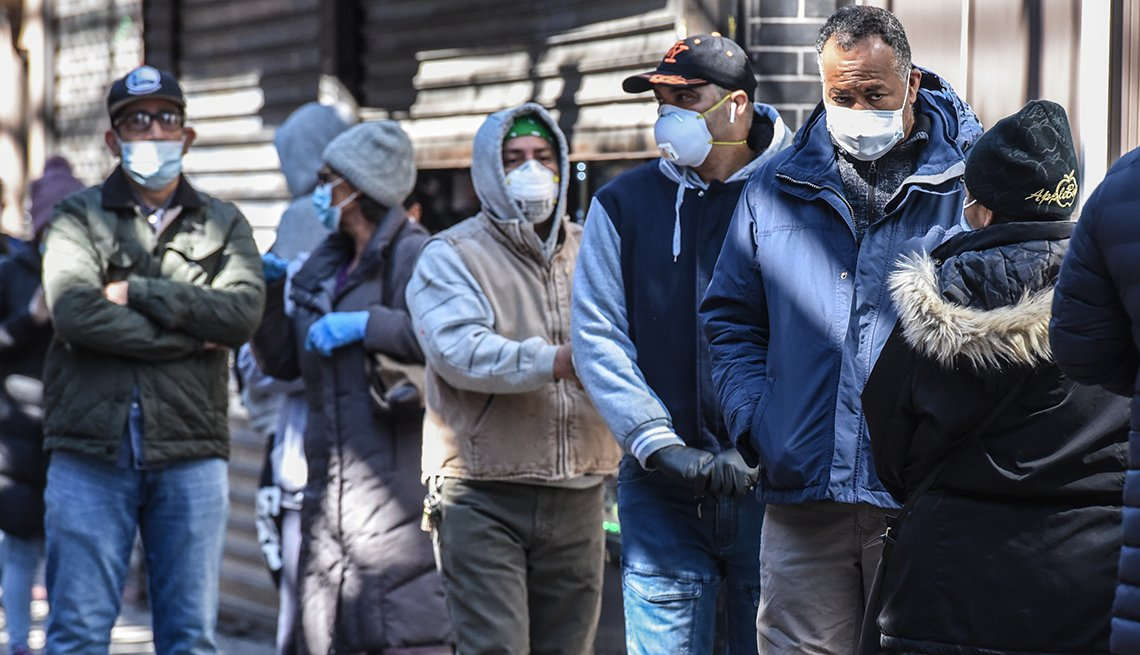 People wait in line wearing face masks