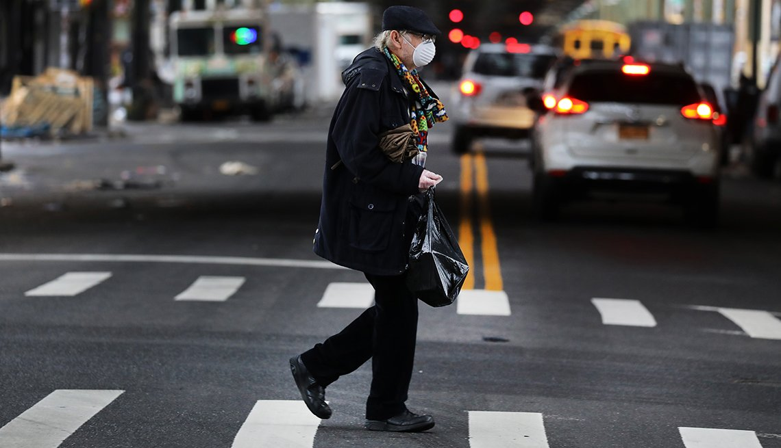 person wearing protective mask crosses the street in the Borough Park section of Brooklyn