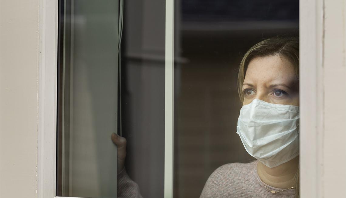Mujer con una máscara en la cara mira a través de una ventana.