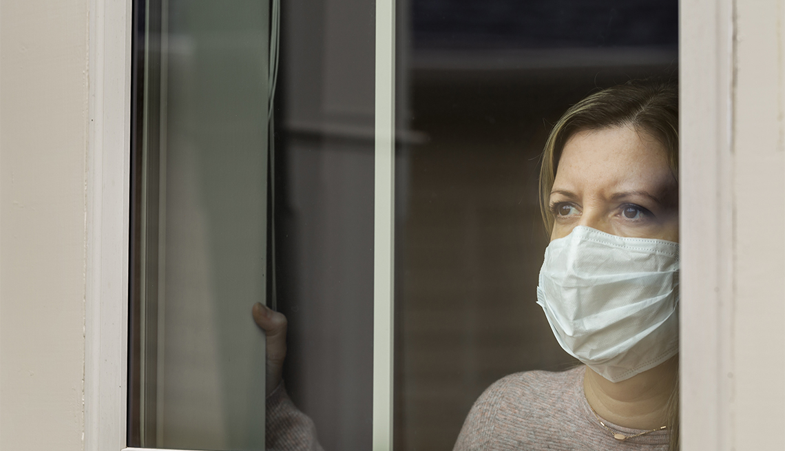 A masked woman in quarantine looks out the window of her home.