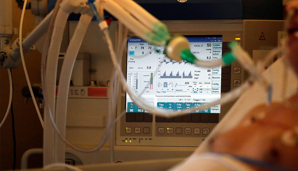 A picture shows a monitor with a breathing machine on an intubated and sedated patient infected with COVID-19.