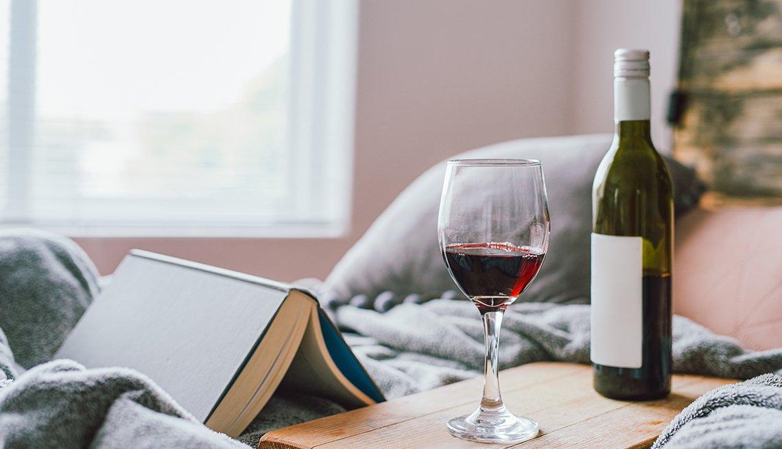Un libro, una copa de vino y una botella sobre una cama