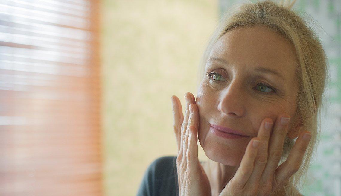 Mujer toca su rostro mientras examina sus ojos