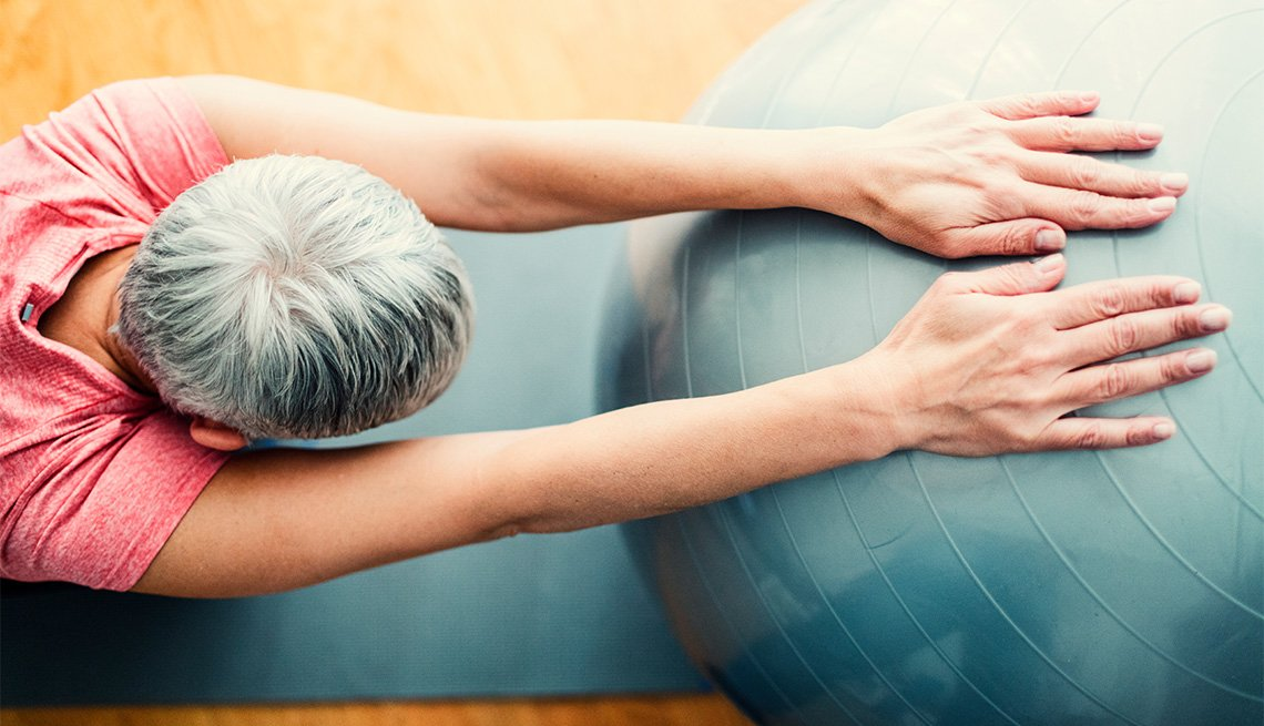 Mature woman exercising at home. Sitting on exercise mat and working stretching exercise while holding hands on pilates ball. Overhead view.