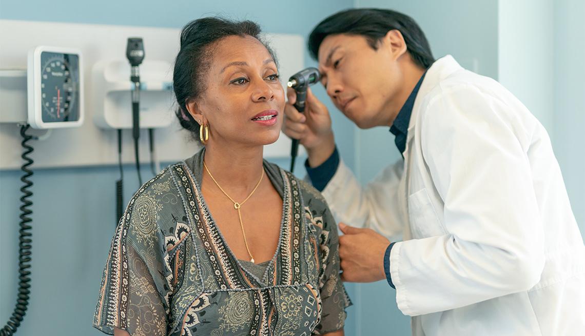 Un médico examina los oidos de una paciente