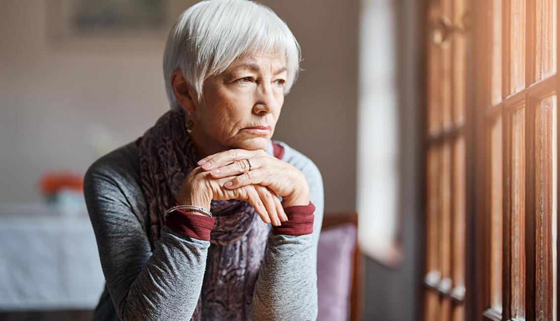 Una mujer mayor triste mira por una ventana