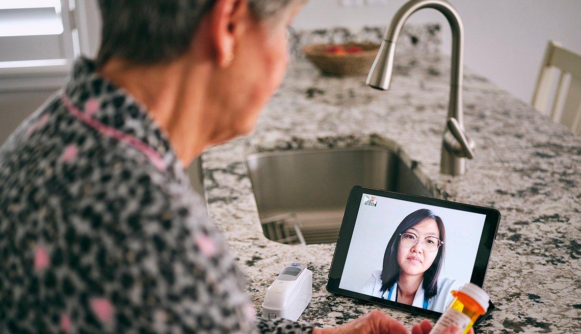 Una mujer consulta a su doctora vía una videollamada