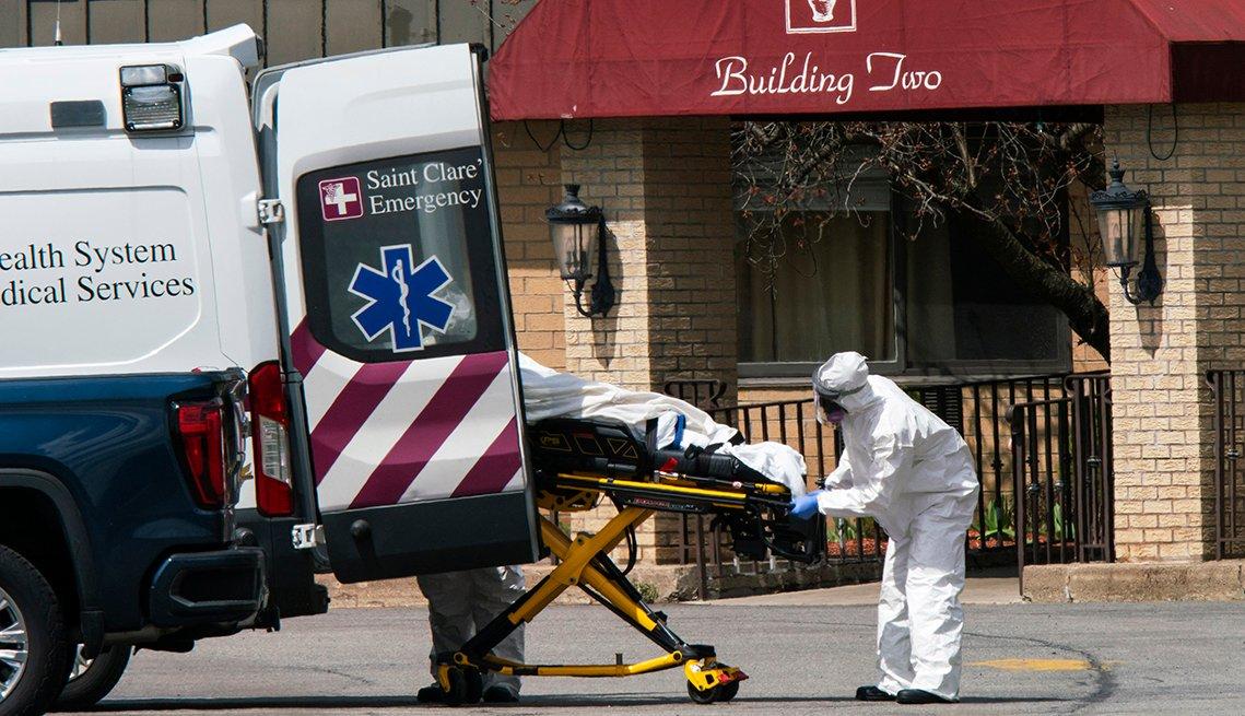 Empleados médicos suben una persona fallecida a una ambulancia