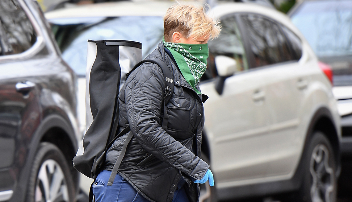 Woman walking through a parking lot wearing a green bandana as a face mask