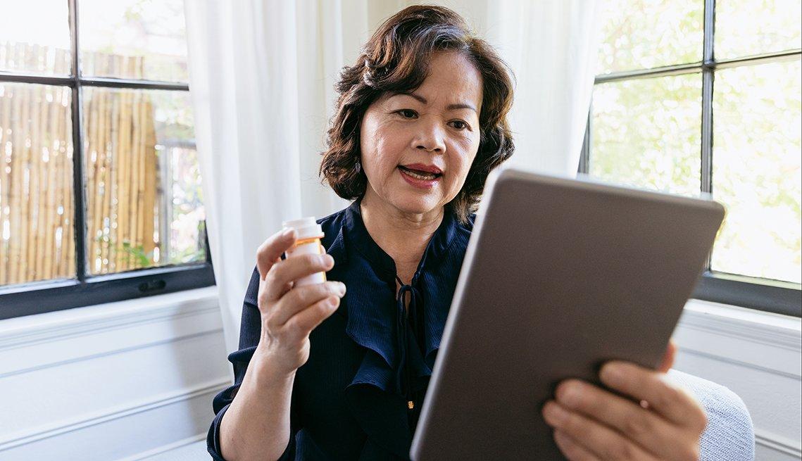 Una mujer sostiene un frasco de pastillas mientras consulta a su médico de forma virtual