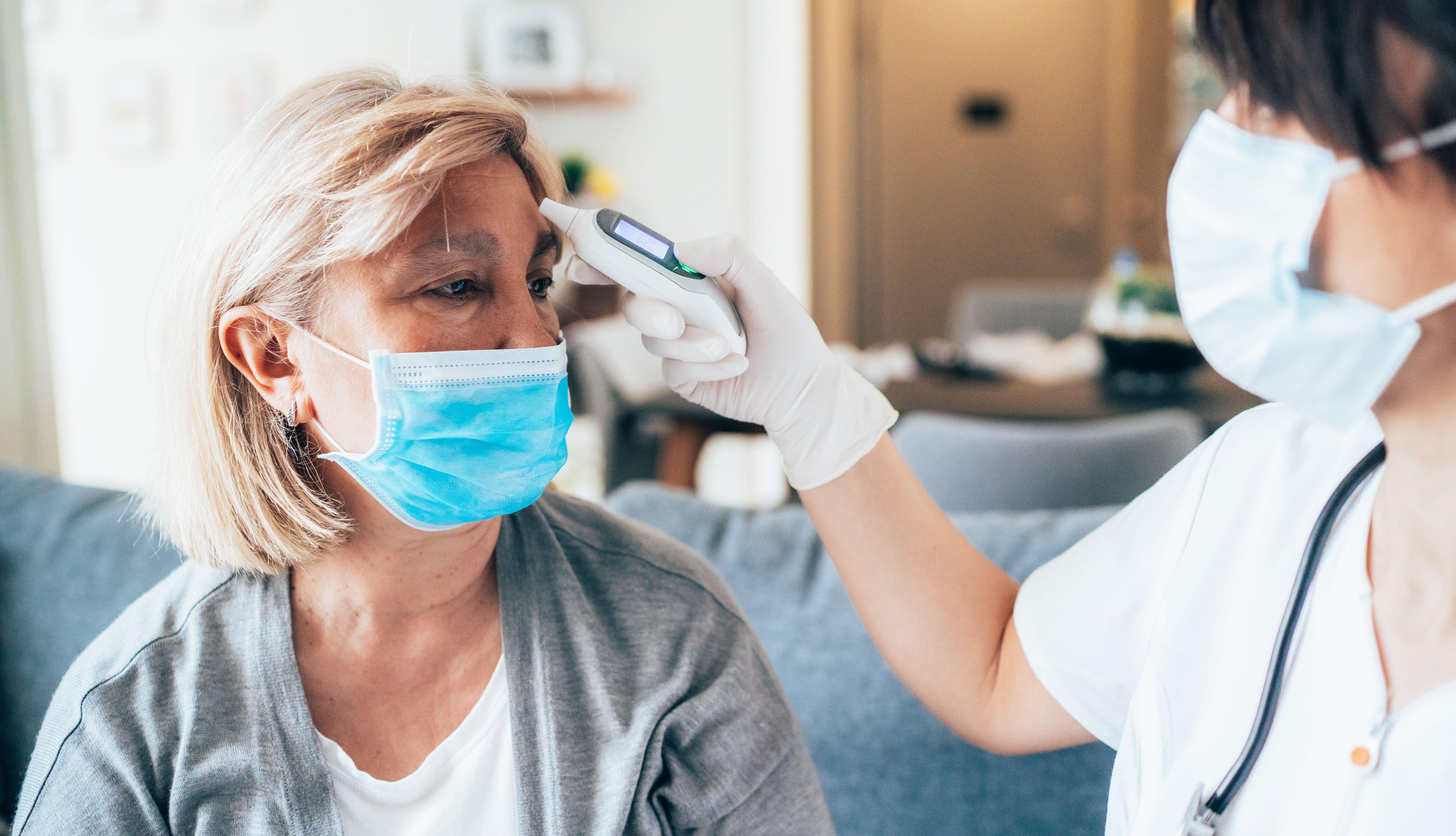 female patient getting her temperature taken