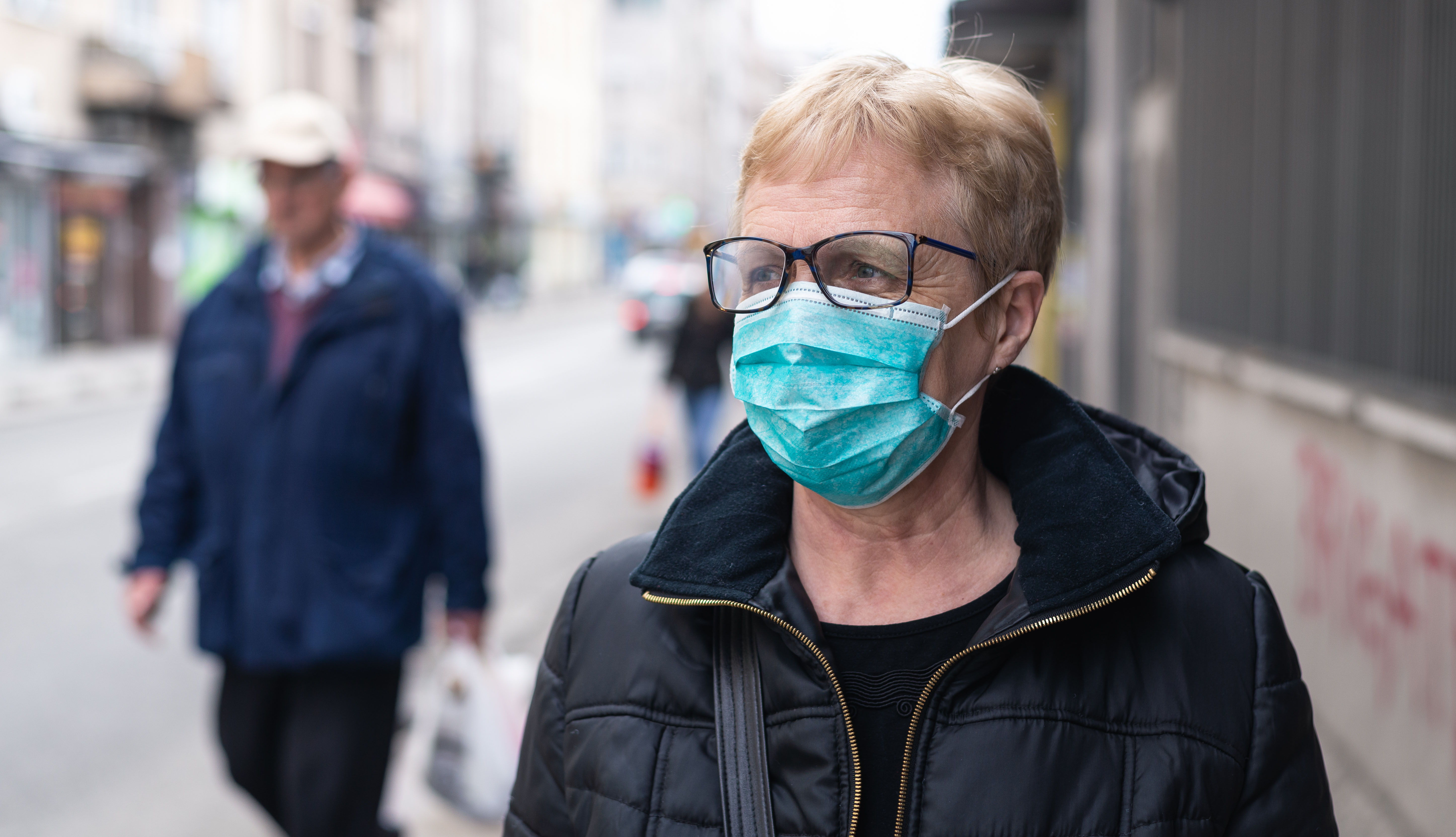 woman on the street wearing mask looking wary of other pedestrians