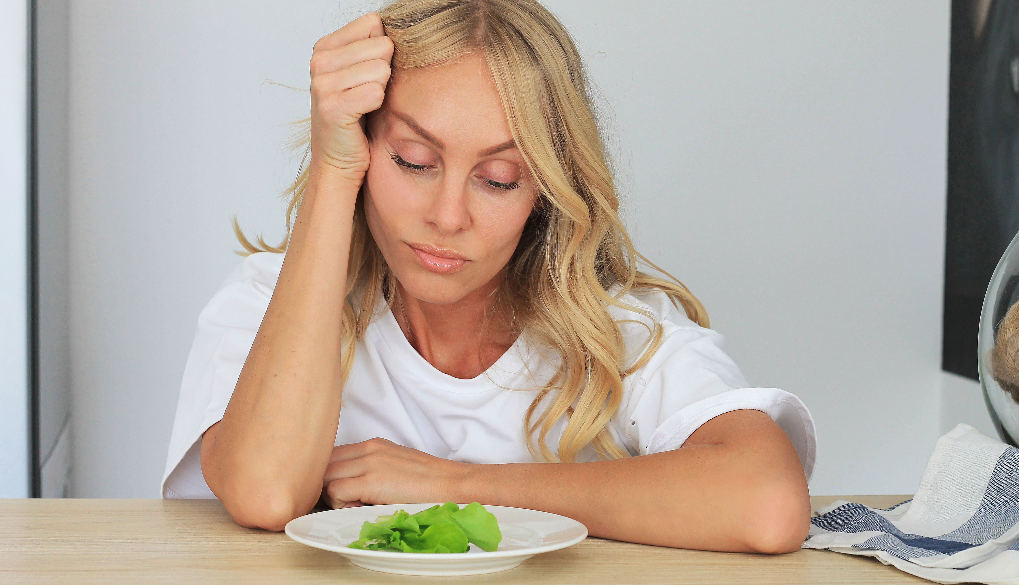 Una mujer sin apetito mira un plato de comida