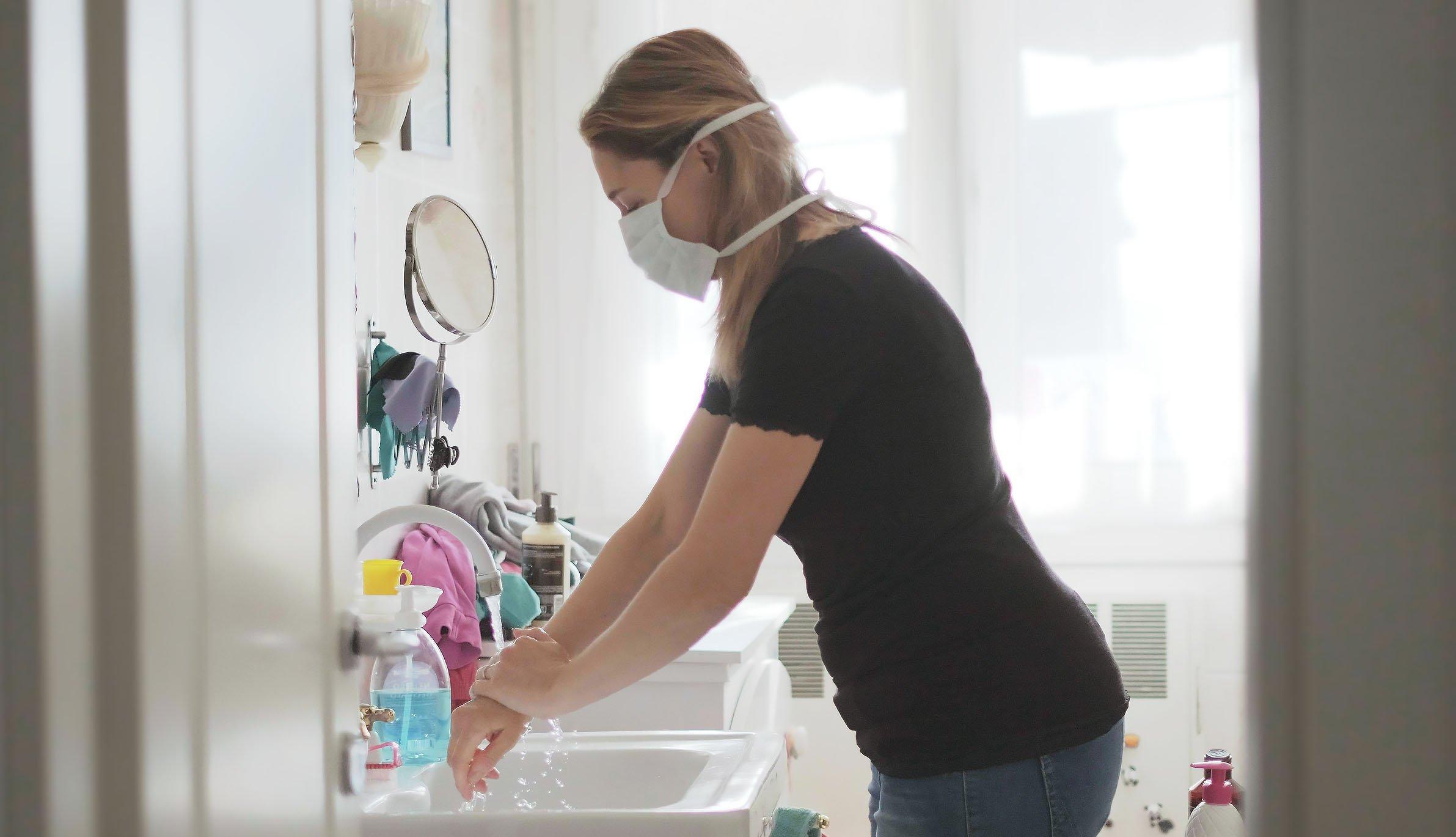 Una mujer, usando mascarilla, se lava las manos