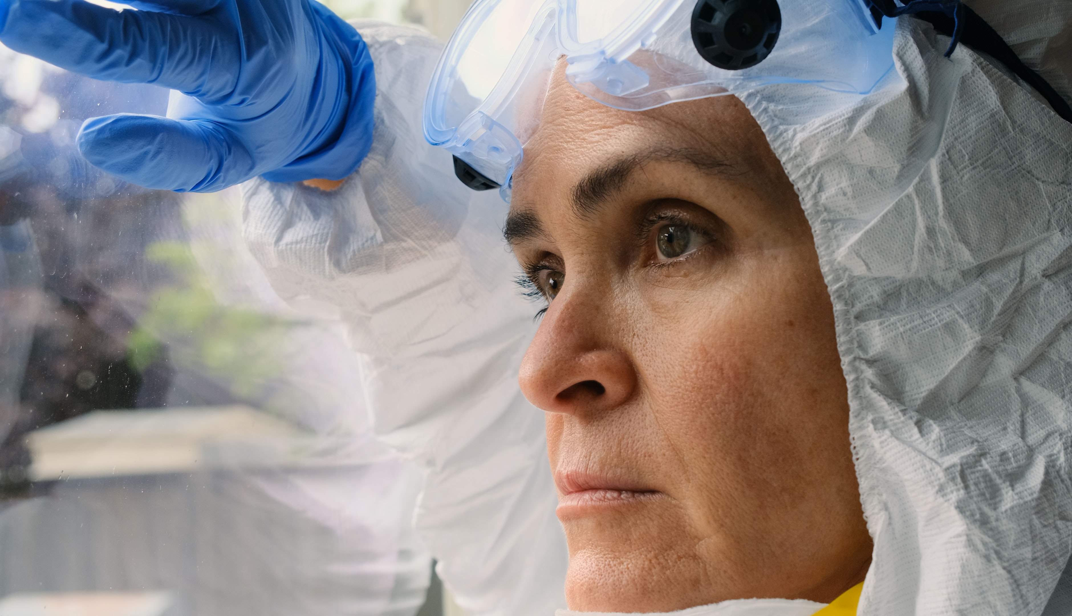 health care worker wearing protective gear looking out a window. She appears sad and stressed.