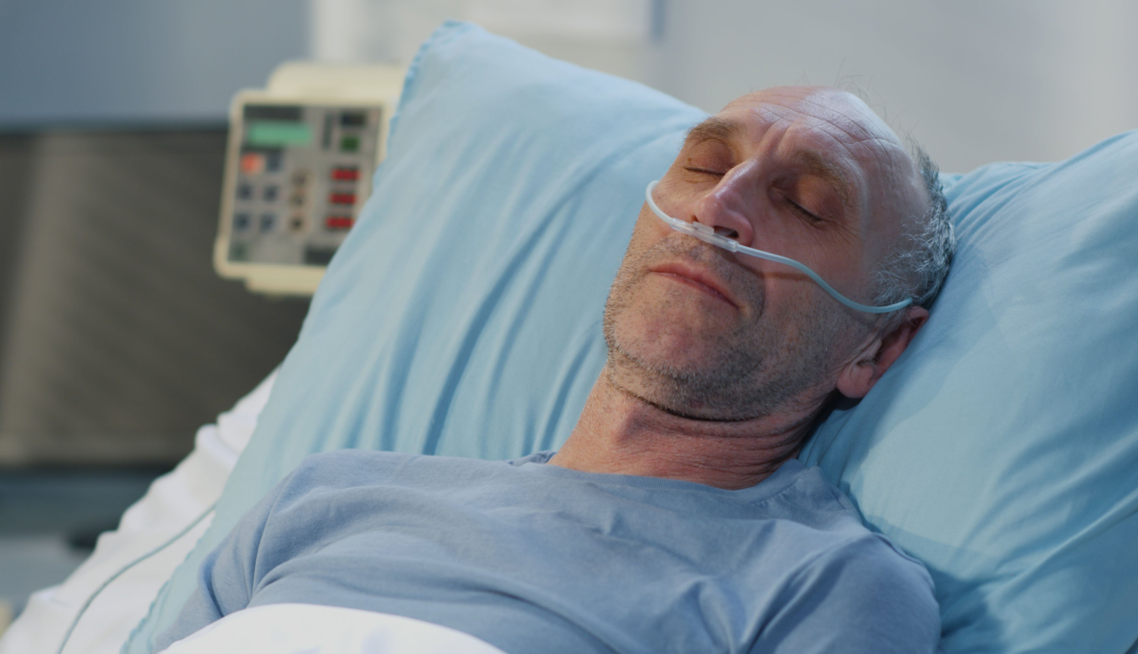 close up of male patient lying in hospital with a nasal canula in his nose to help with oxygen
