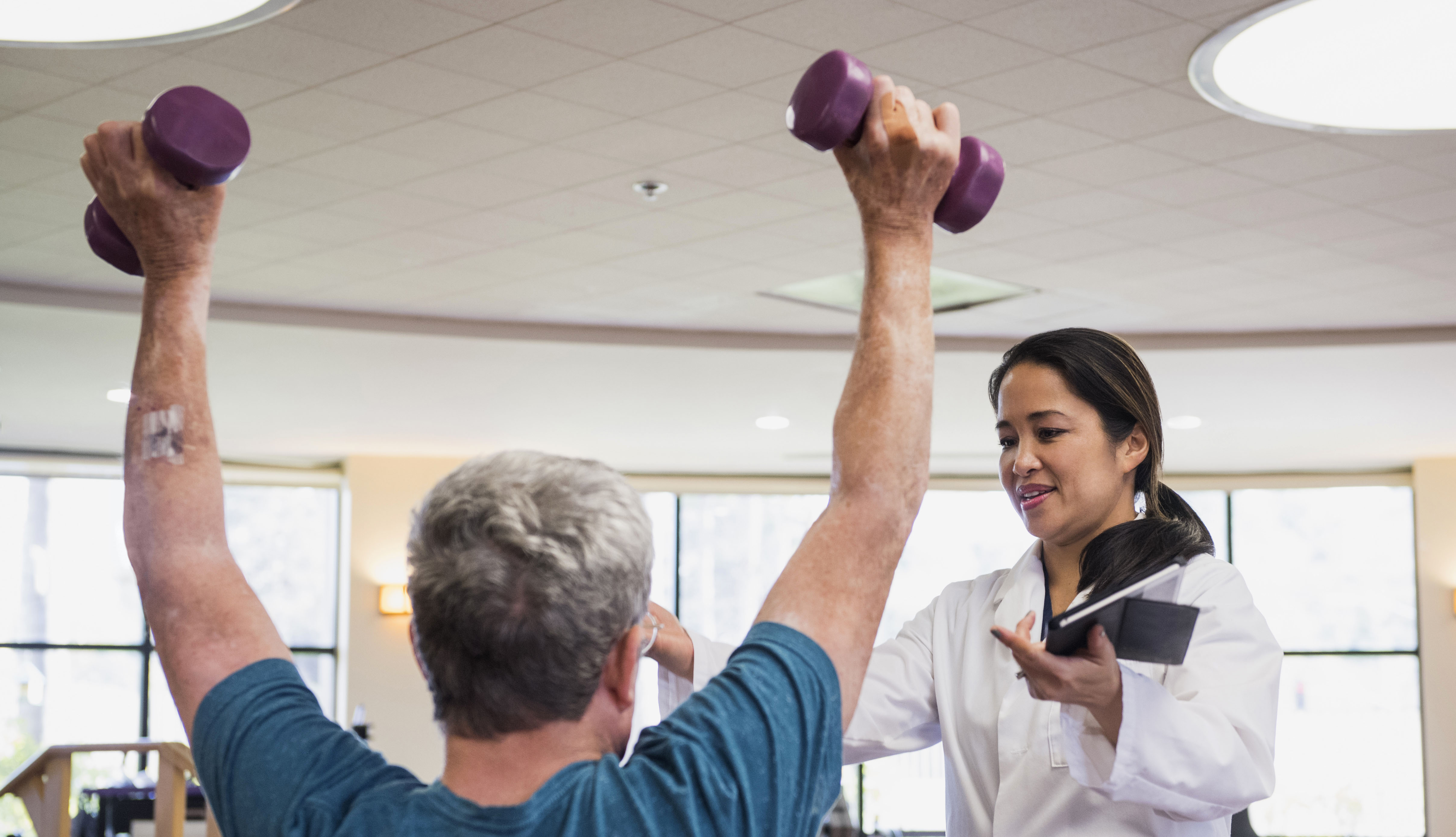 physical therapist helping patient lifting light weights