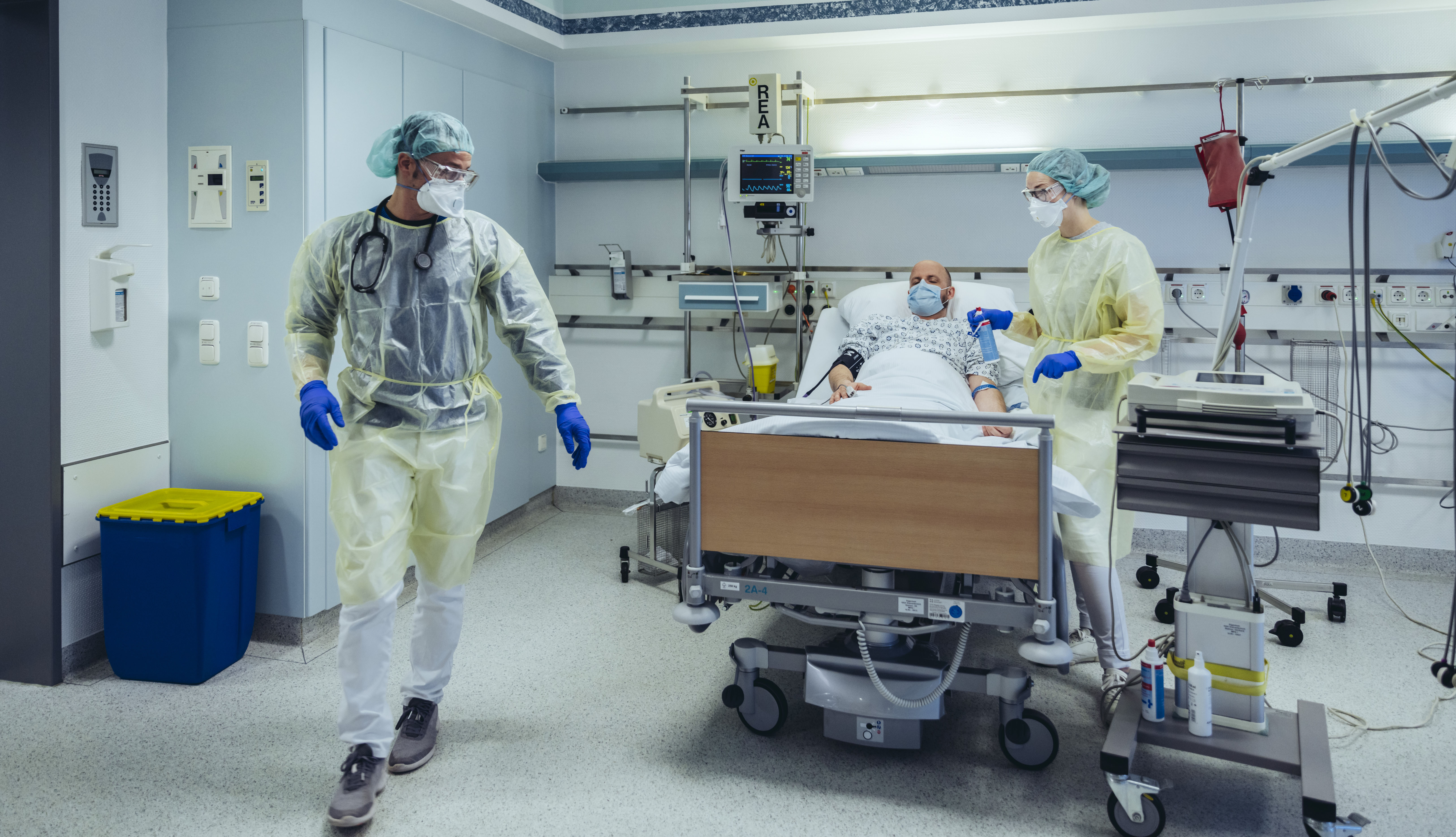 Empleados de hospital con equipo protector atienden a un paciente en camilla