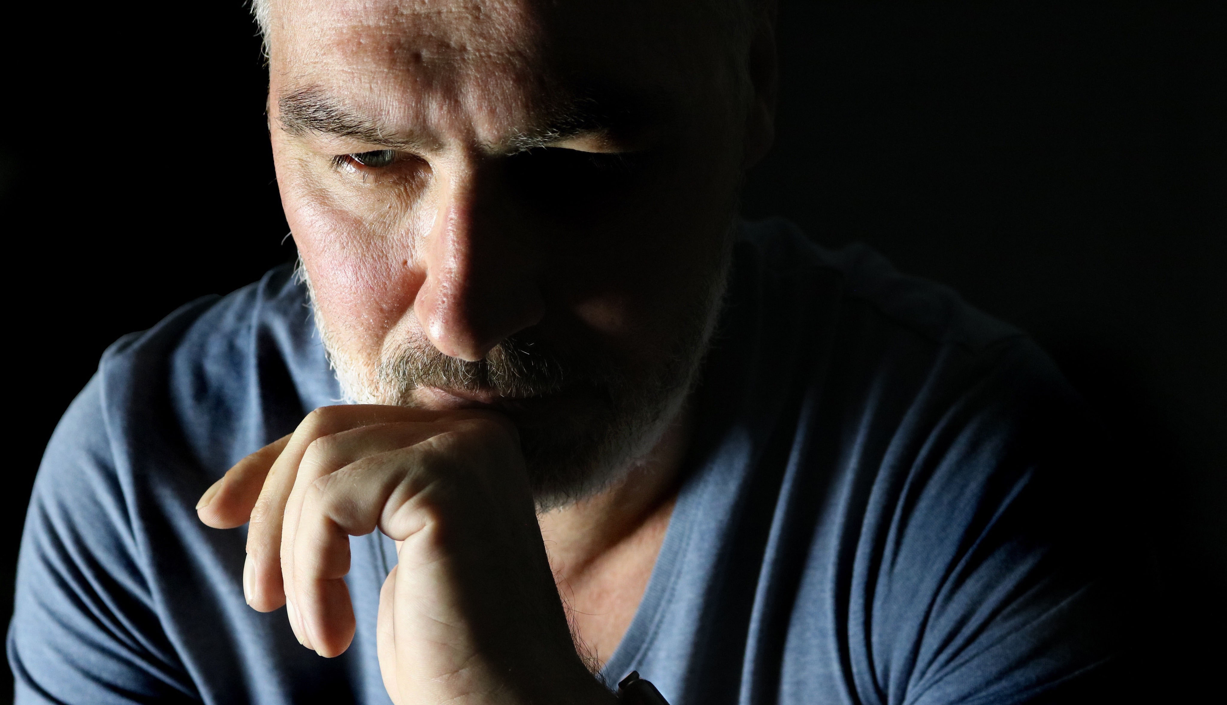 close up of a man looking sad and confused, set against a black background