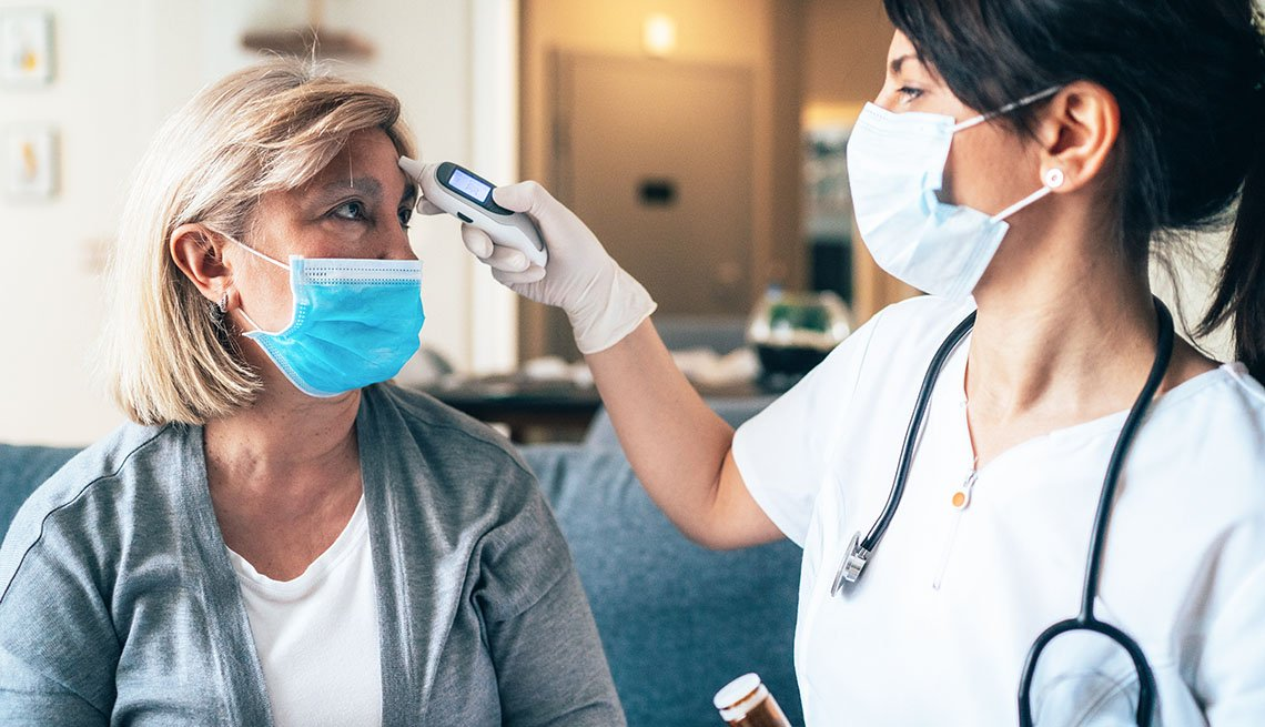 Una enfermera le toma la temperatura a una paciente