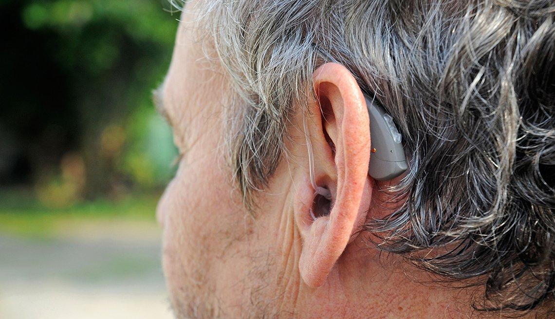 Un hombre que usa audífonos para oir mejor