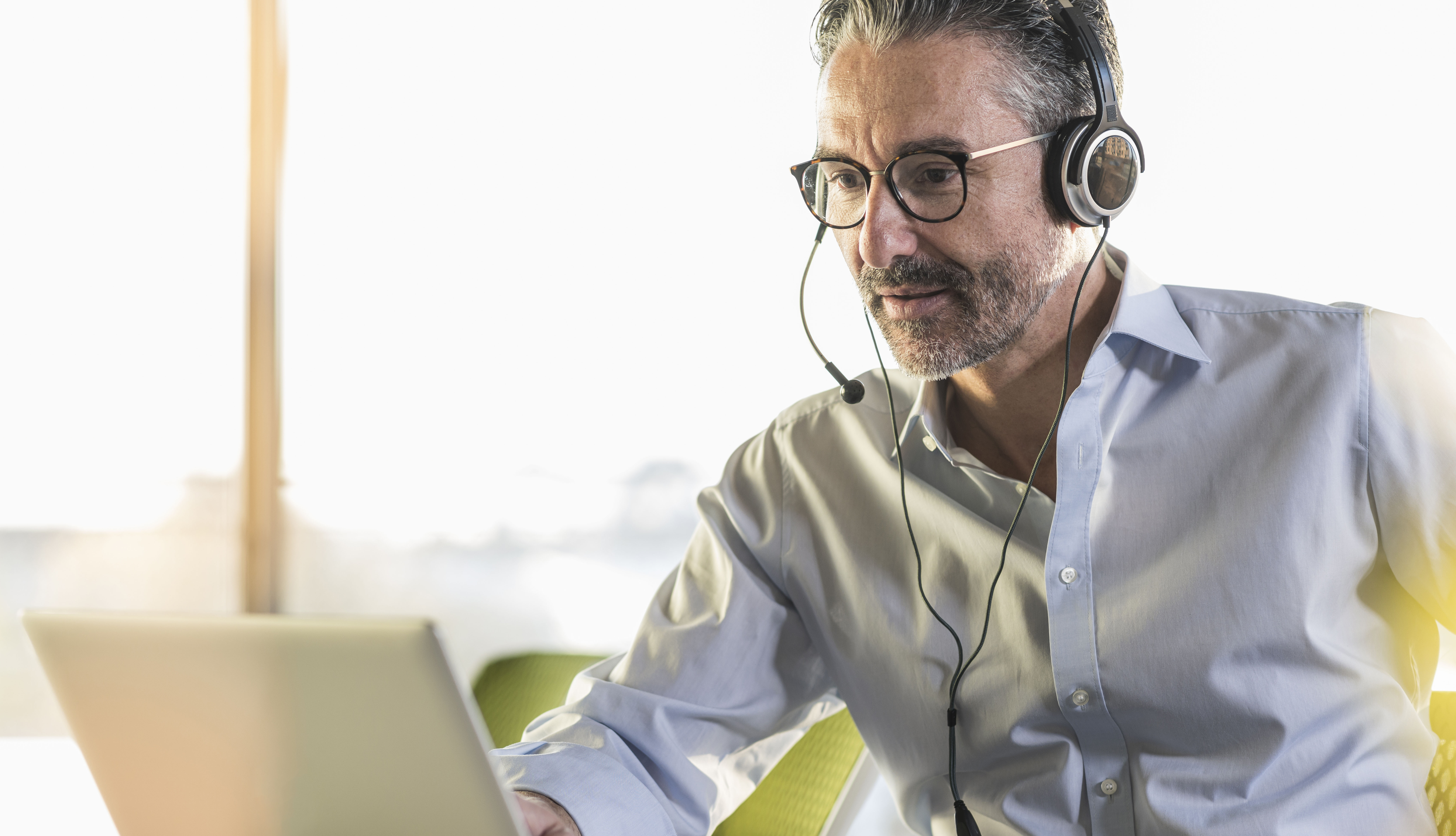 man wearing headset participating in videoconference call on laptop.
