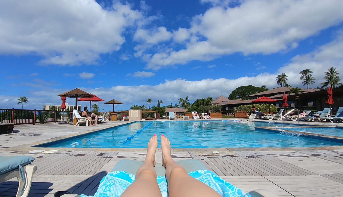 wide view of a public pool from a lounge chair with a womans legs in foreground