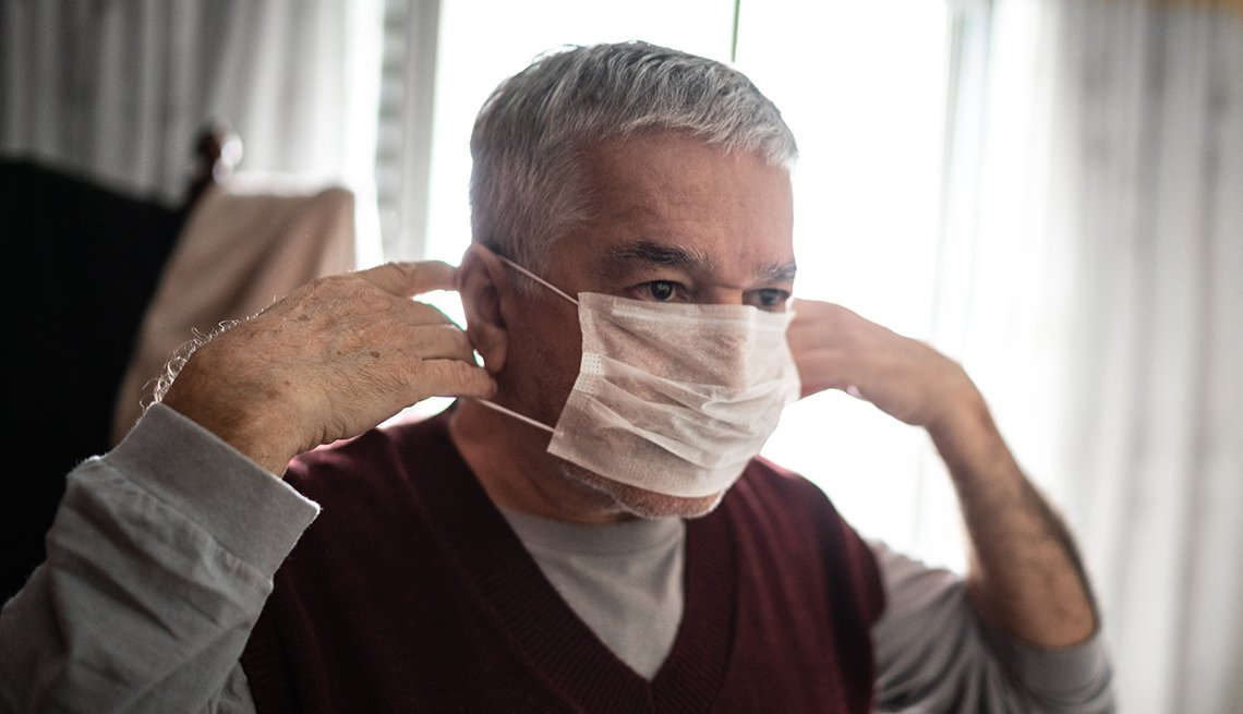 man putting on a protective mask for coronavirus at home