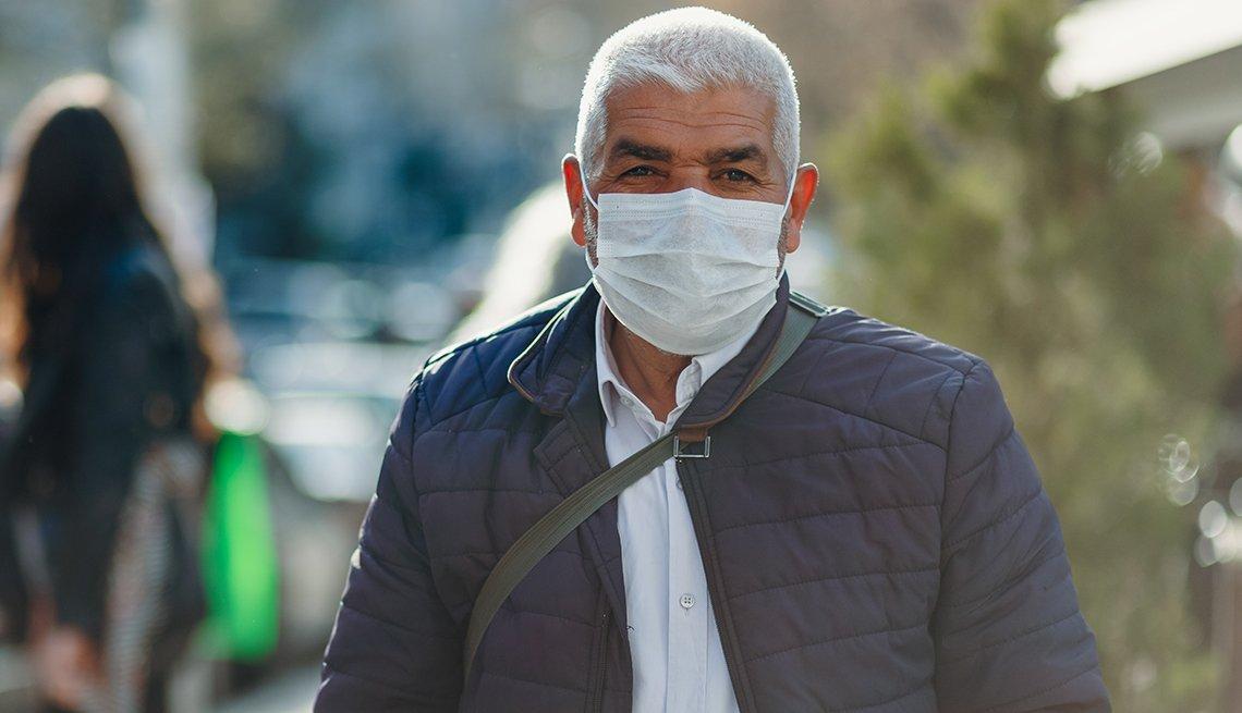 Un hombre usa una mascarilla mientras camina al aire libre