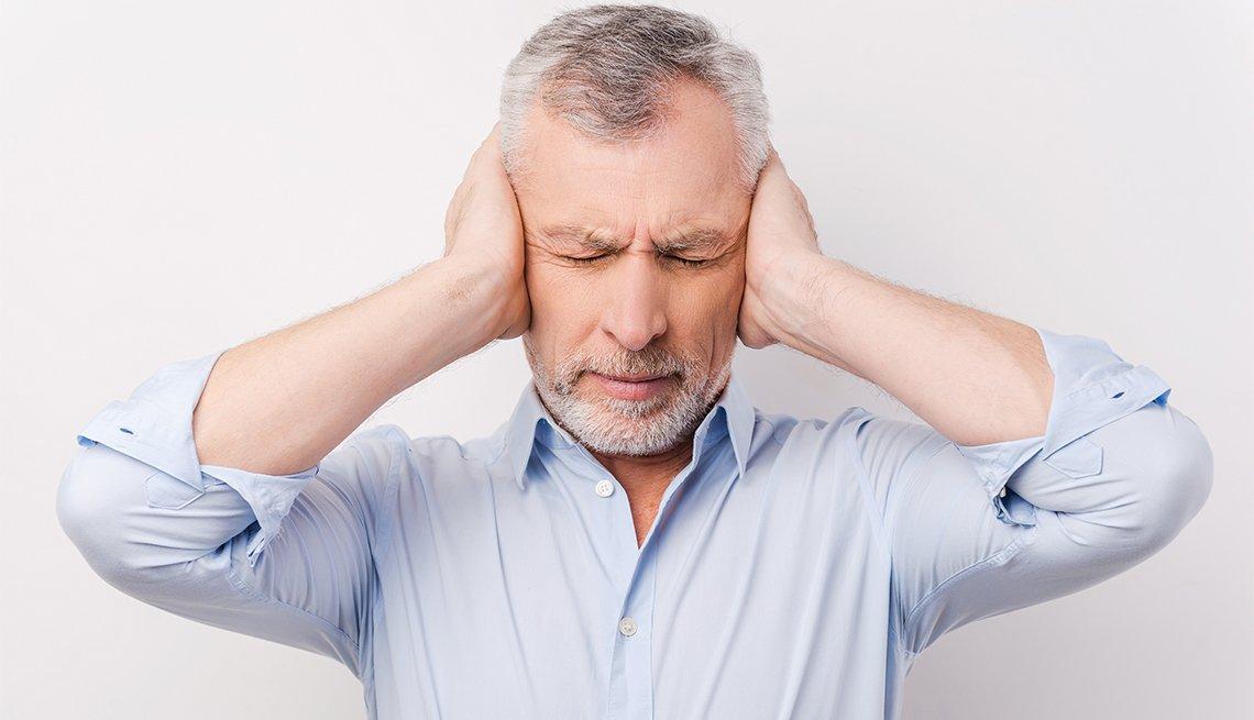 Un hombre se tapa los oídos con sus manos
