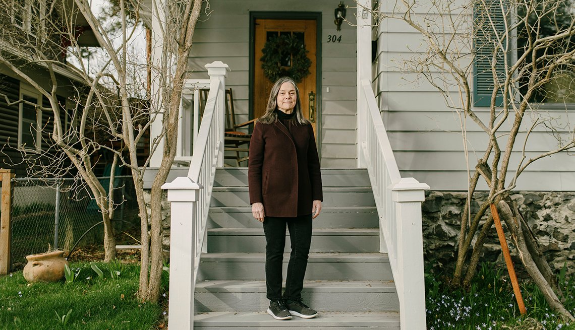 a woman standing on the front steps of her house