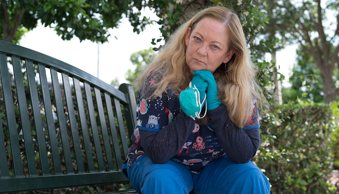 a nurse sits on a park bench outdoors resting her chin in her hands