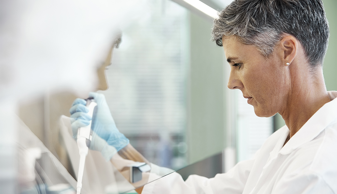 medical researcher uses a pipette while working on an experiment