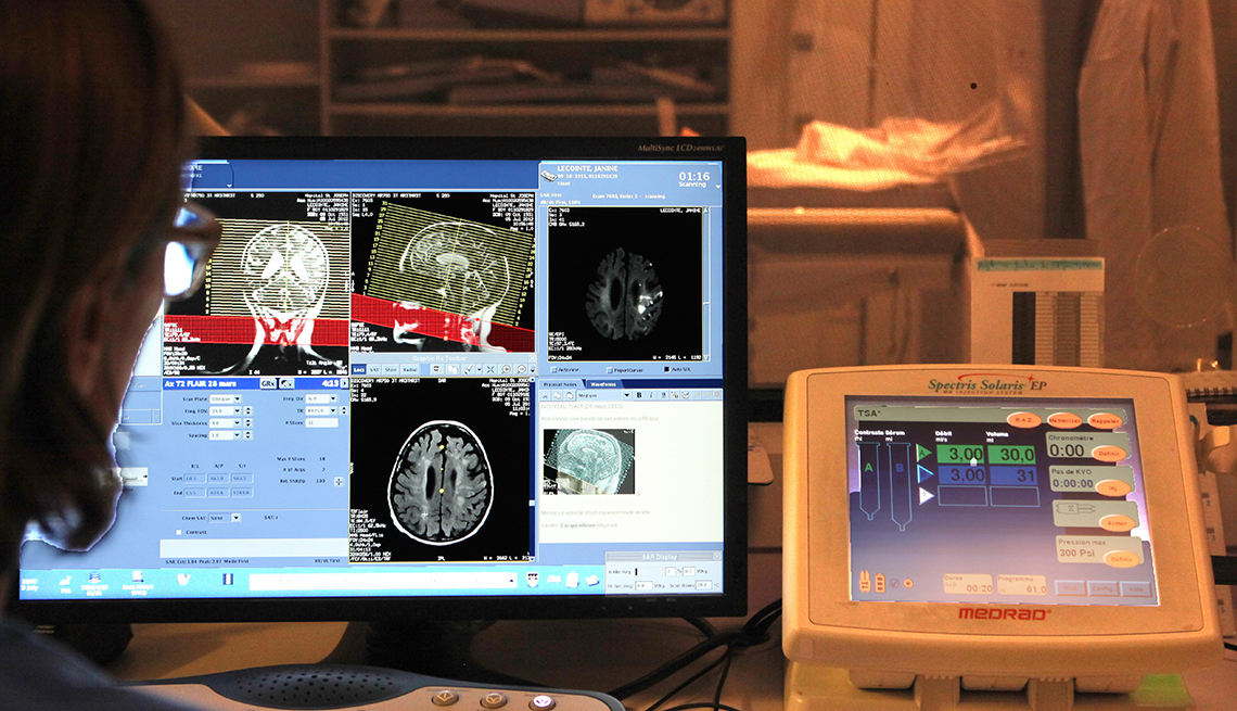 a technician looks at a monitor screen of brain scans and an m r i instrument panel