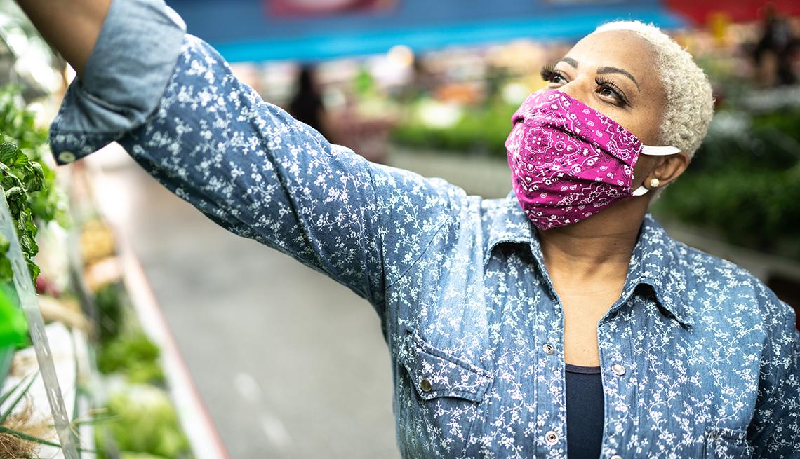 Una mujer, usando mascarilla, en un supermercado usan