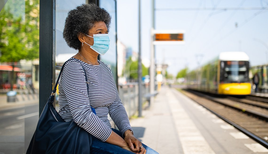 woman on train platform wearing a medical mask