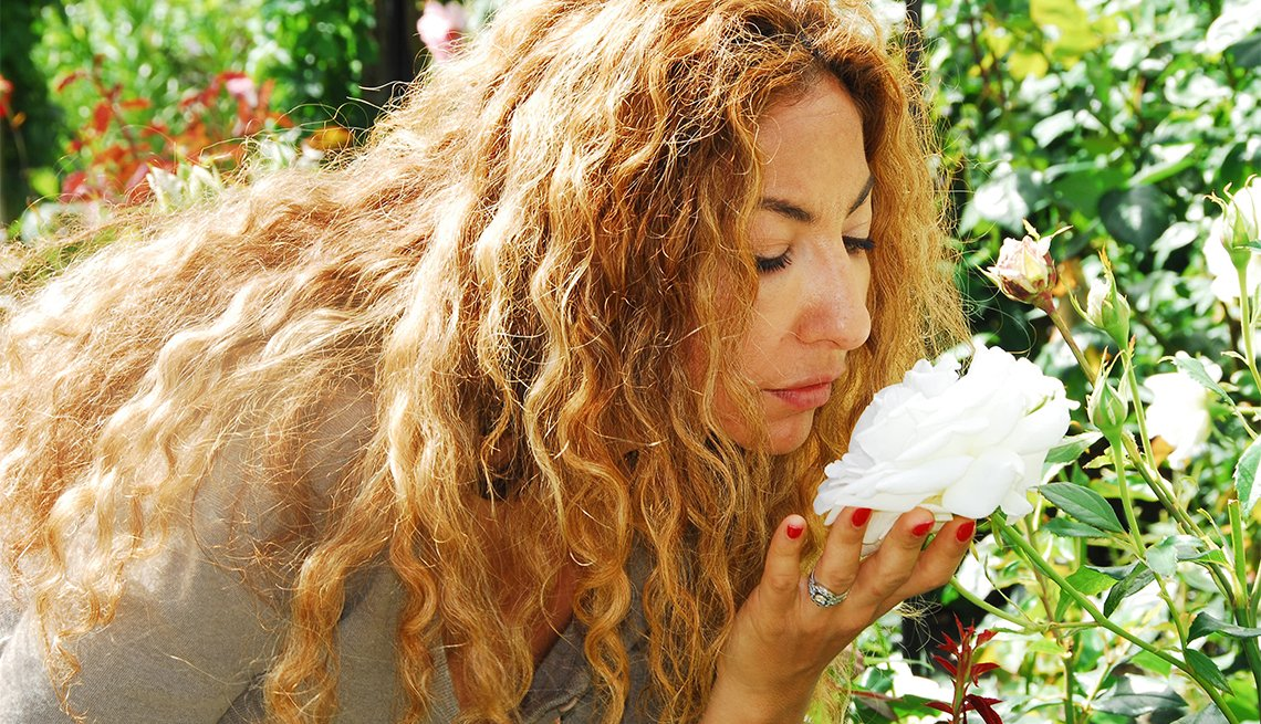 woman bends over to smell a big white flower in a garden
